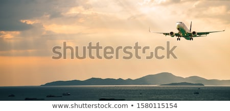 Stock photo: Landscape with white passenger airplane, mountains, sea and oran