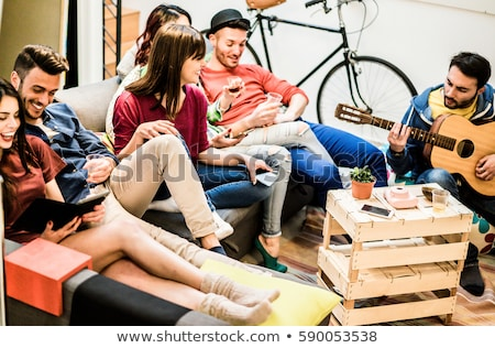 Group of trendy hipsters men and women laughing, and playing gui Stock photo © deandrobot