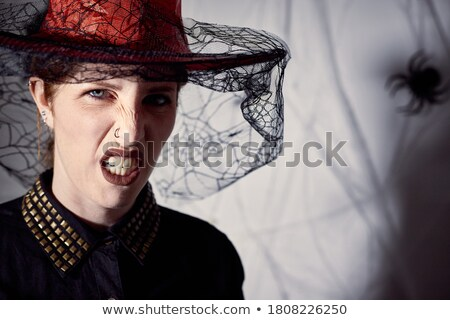 Scary wizard woman wearing black costume and halloween makeup lo Stock photo © deandrobot