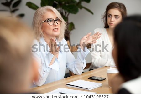 Team of mature women and men at meeting table stock photo © frimufilms