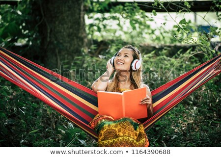 Woman In Hammock Reading The Book On Mobile Phone Stock photo © AndreyPopov