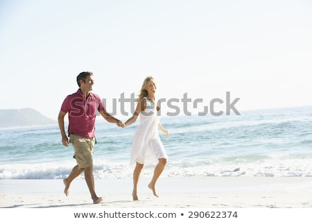 Romantic Young Couple Running Along Shoreline Of Beach Holding H Stock photo © monkey_business
