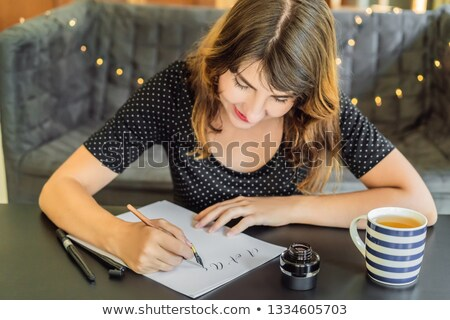Calligrapher Young Woman writes phrase on white paper. Bible phrase about love Inscribing ornamental Stock photo © galitskaya