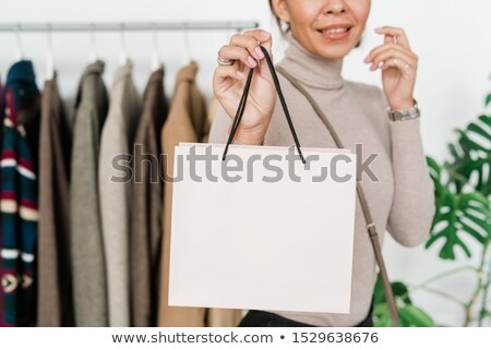 Happy young shopaholic in casualwear holding white paperbag in front of camera Stock photo © pressmaster