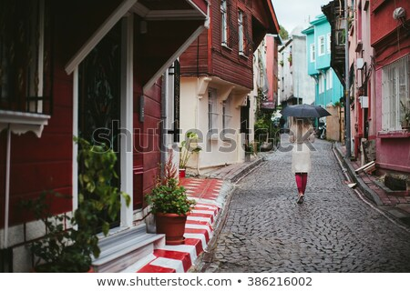 A woman in an elegant black coat walks through the city in a tunnel between houses Stock photo © ElenaBatkova