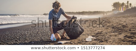Young man cleaning up the beach. Natural education of children Stock photo © galitskaya