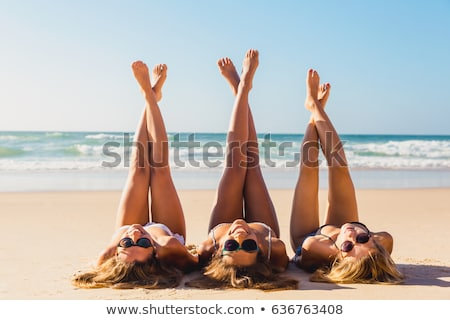 Three young people lying in the sand Stock photo © photography33