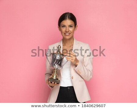 casual woman holds her trophy and smiles stock photo © feedough