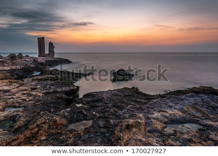 Sunset over the Sea and Rocky Coast with Ancient Ruins Stock photo © Kayco