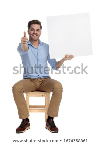 man showing positive hand gesture while sitting in studio Stock photo © feedough