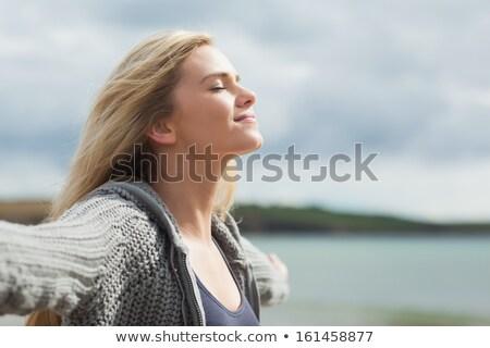 Vista lateral mulher brasão céu em pé praia Foto stock © wavebreak_media