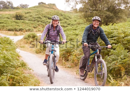 Senior couple cycling on country lane Stock photo © IS2