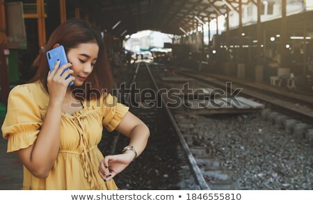 Young asian traveler holding alarm clock. Stock photo © RAStudio