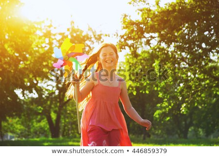 girl blowing windmill in sun stock photo © is2