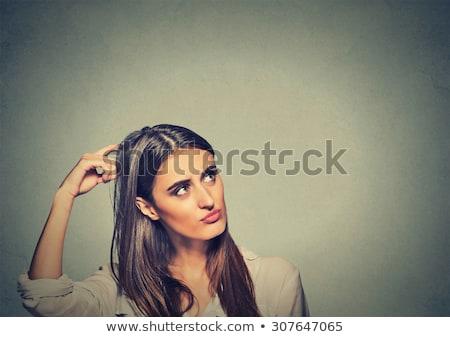 Young hispanic woman scratching her head. Stock photo © RAStudio