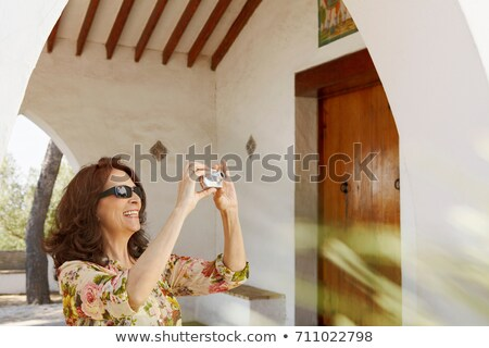 Older tourist woman taking a snapshot Stock photo © IS2
