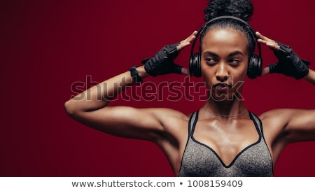 strong young sports woman listening music with headphones stock photo © deandrobot