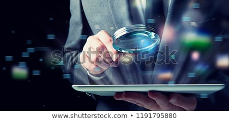 businessman examines a tablet with a magnifying glass concept of internet security stock photo © alphaspirit