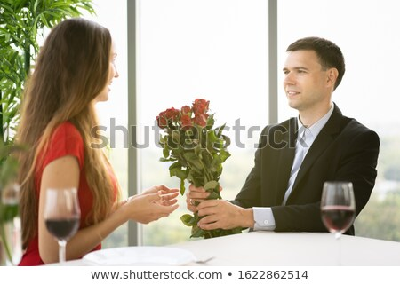 happy husband giving flowers to his wife at home stock photo © dolgachov