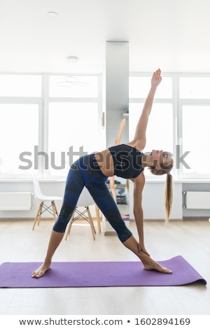 Slender young woman doing exercises with weights in the gym Stock photo © boggy