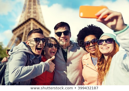 happy friends showing thumbs up over eiffel tower Stock photo © dolgachov