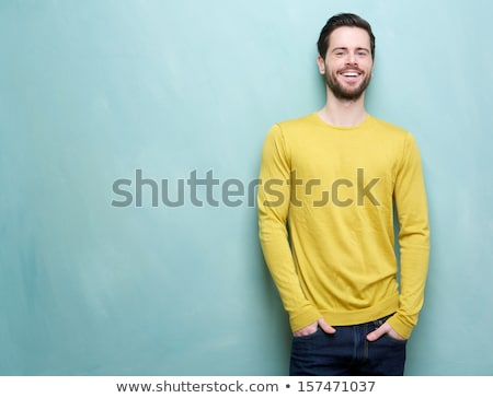 portrait of a happy young bearded man standing stock photo © deandrobot