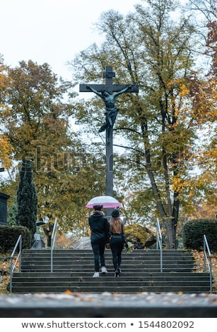 Man and woman walking up steps on cemetery towards a cross Stock photo © Kzenon
