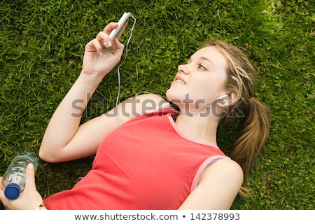 A young woman lay down and take a rest on the green grass Stock photo © Lopolo