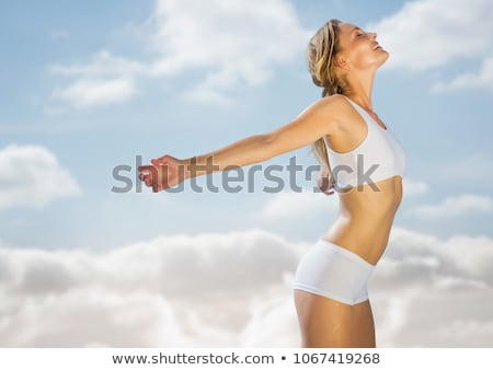 Woman soaking up sun against blurry sky Stock photo © wavebreak_media