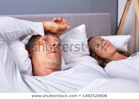 Man With Insomnia Lying On Bed Next To His Wife Stock photo © AndreyPopov