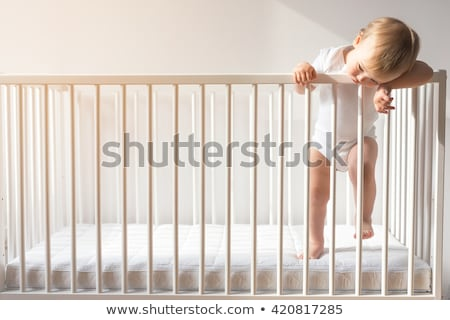 a crying baby girl at home on the baby room stock photo © lopolo