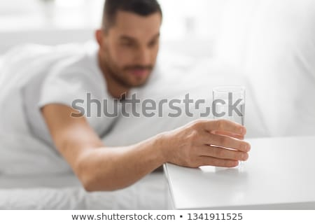 close up of man in bed reaching to glass of water Stock photo © dolgachov