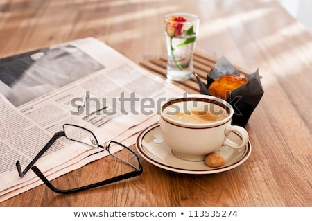 Stock photo: Cup of coffee, newspaper and graphs