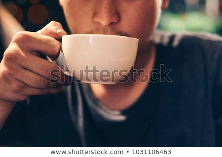 Young man drinking coffee in the restaurant at night Stock photo © zurijeta
