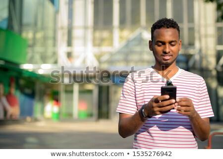 笑みを浮かべて 魅力的な 男 巻き毛 携帯電話 ベッド ストックフォト © deandrobot