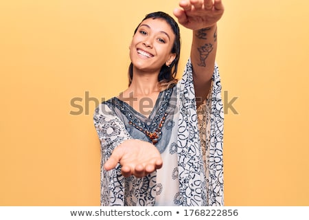 Young hippie woman standing with raised arms up. Stock photo © RAStudio
