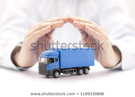 Car insurance. Blue truck miniature covered by hands.  Stock photo © sqback