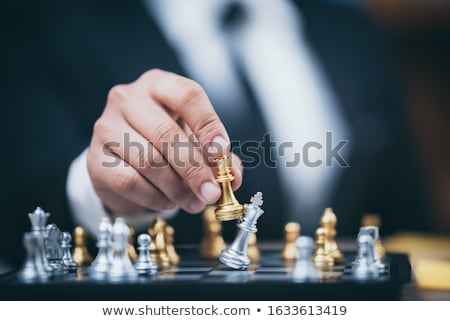 hand of businessman moving chess figure in competition board gam stock photo © snowing