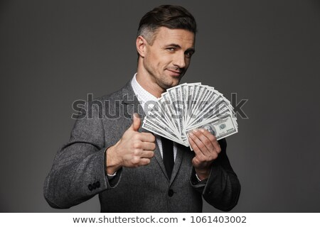 Stock photo: Image of businessman 30s in suit holding fan of dollars and smar