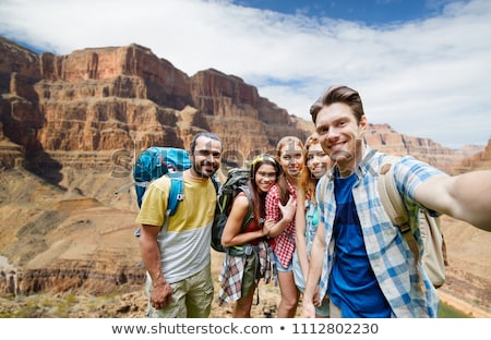 smiling woman with backpack over grand canyon Stock photo © dolgachov
