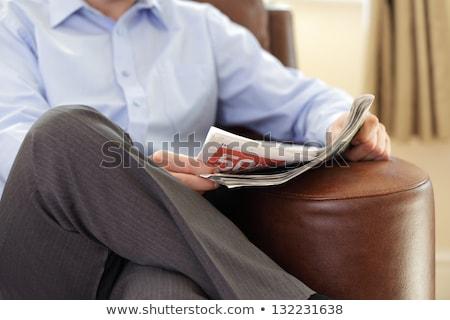 Férfi ül szék lábak keresztbe olvas újság Stock fotó © feedough