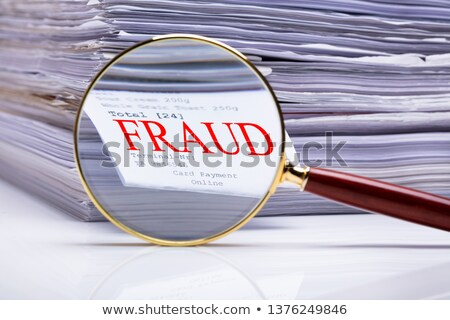Stockfoto: Magnifying Glass On Fraud Text Near Stacked Paper