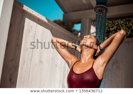 woman at sea bathed in a shower and tans in the sun stock photo © elenabatkova