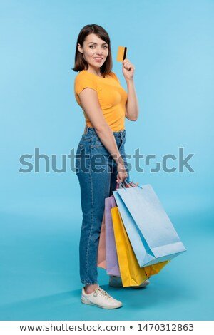 Stock photo: Successful female shopper with paperbags showing credit card