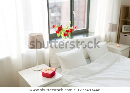 gift in shape of heart on bedside table in bedroom stock photo © dolgachov