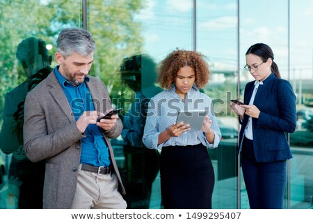 Three young contemporary colleagues in formalwear scrolling in mobile gadgets Stock photo © pressmaster