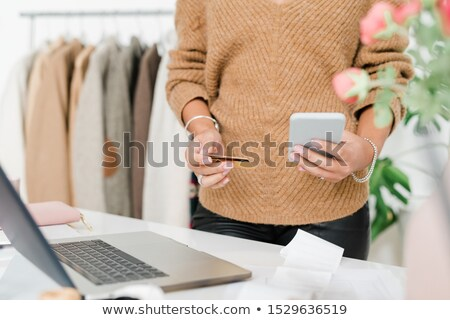 Mid-section of young elegant woman in beige pullover scrolling in smartphone Stock photo © pressmaster