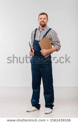 Happy young mechanic in coveralls and shirt holding clipboard and handtool Stock photo © pressmaster