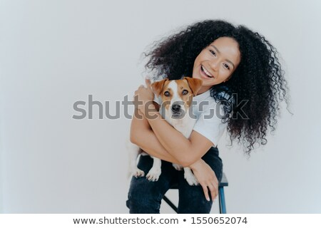Pleasant looking curly girl tilts head, smiles happily, embraces favourite dog, has good time with p Stock photo © vkstudio