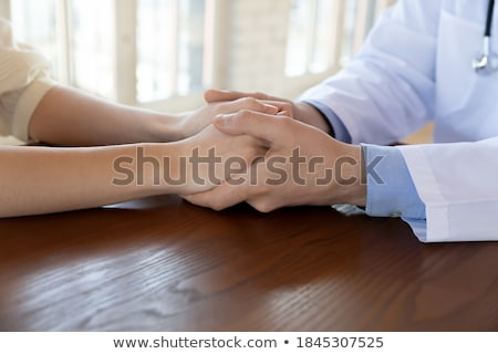 Confident female doctor holds hands of ill patient, persuades everything will be alright, dressed in Stock photo © vkstudio
